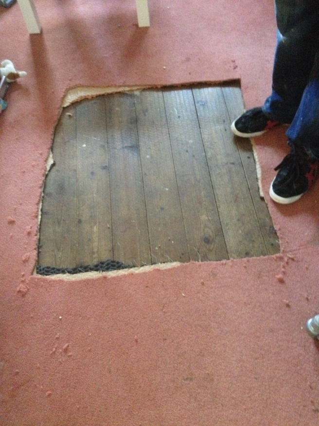 Just cut a hole in the carpet, it's coming up anyway.  Floor sanding guy looks in disbelief then asks for a knife.